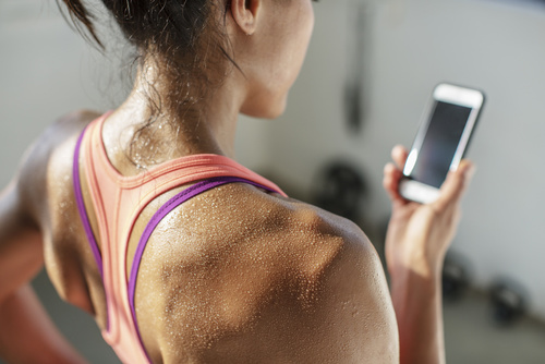 Close-up of female athlete using mobile phone in gym